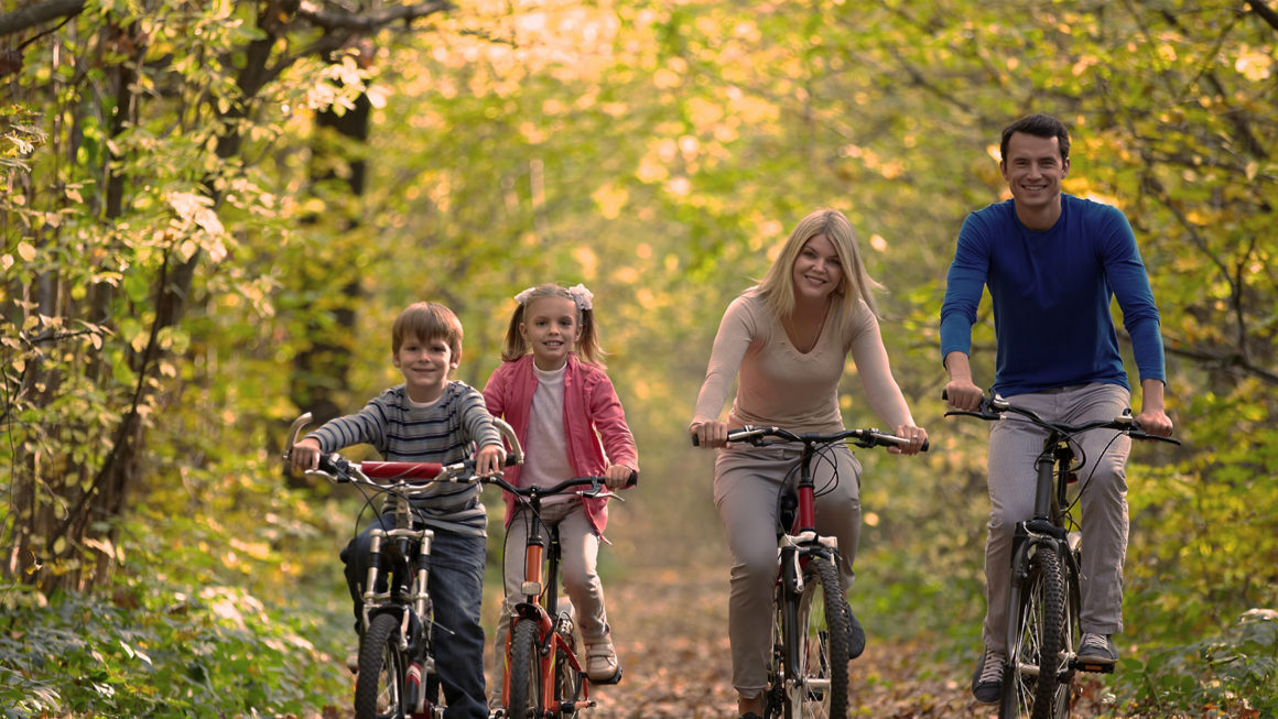 smiling family riding bikes in a park during autumn