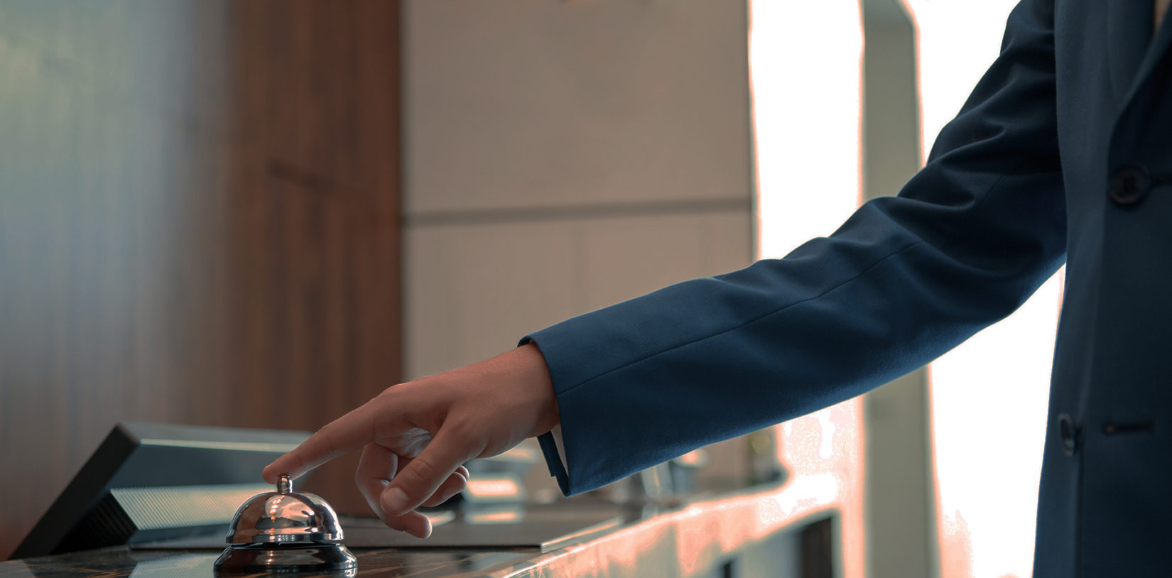 Closeup of a businessman hand ringing silver service bell on hotel reception desk