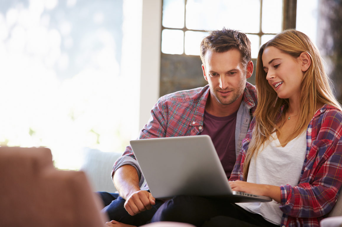 young couple in flannel shirts paying their bills online with a laptop