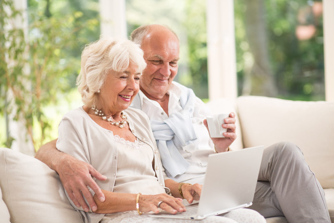 happy elderly couple using a laptop to pay their apartment rent online while drinking coffee