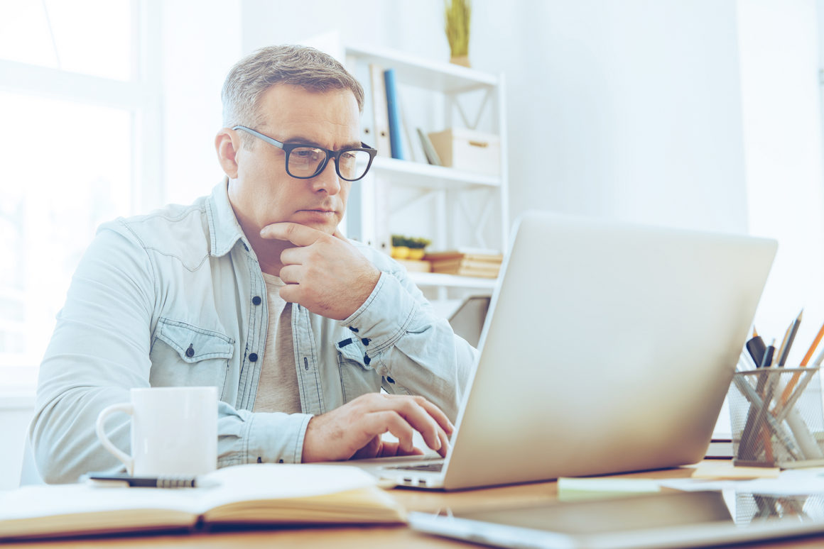 elderly man drinking coffee paying his apartment bill online