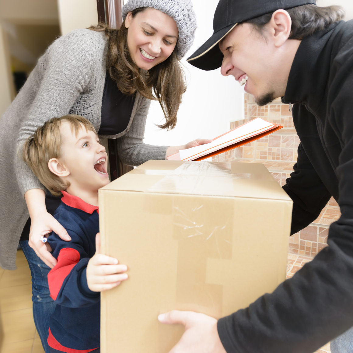 happy child and mother receiving a package from a happy delivery man