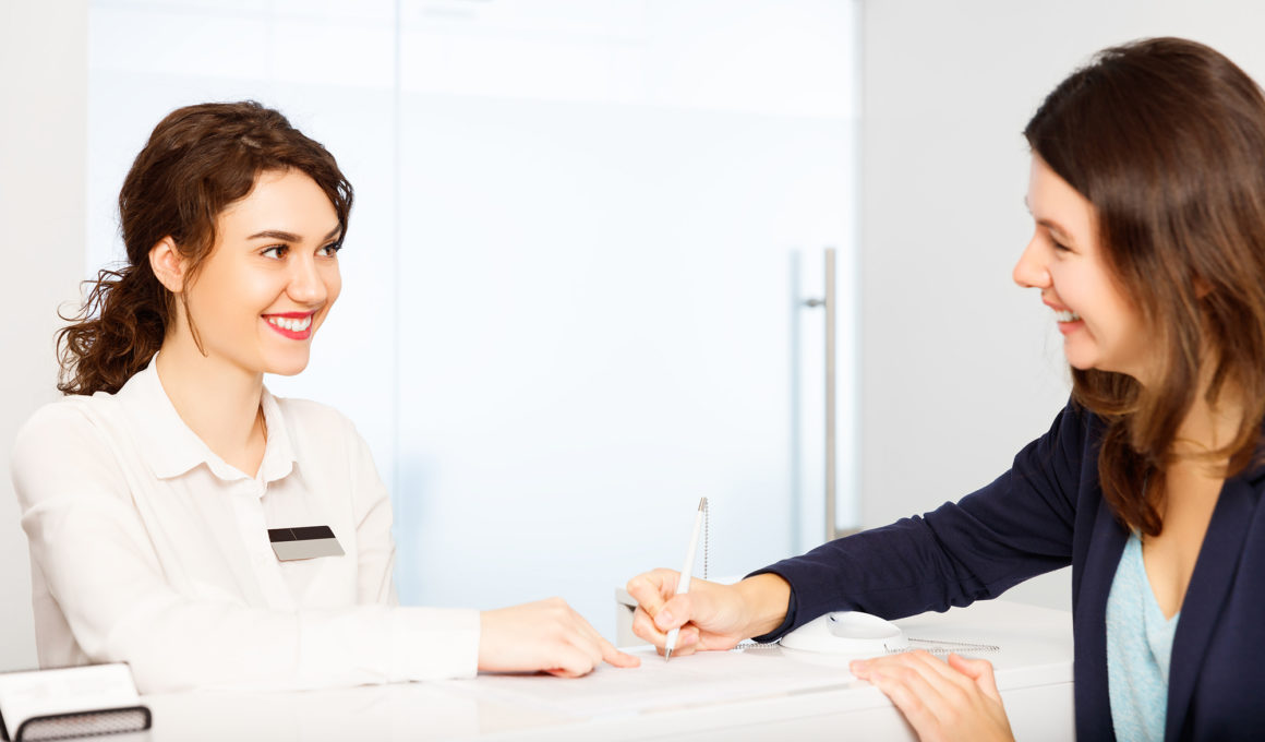 young woman at a concierge desk helping a guest sign a form