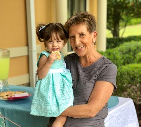 a grandmother happily holding her granddaughter, who is eating a cookie
